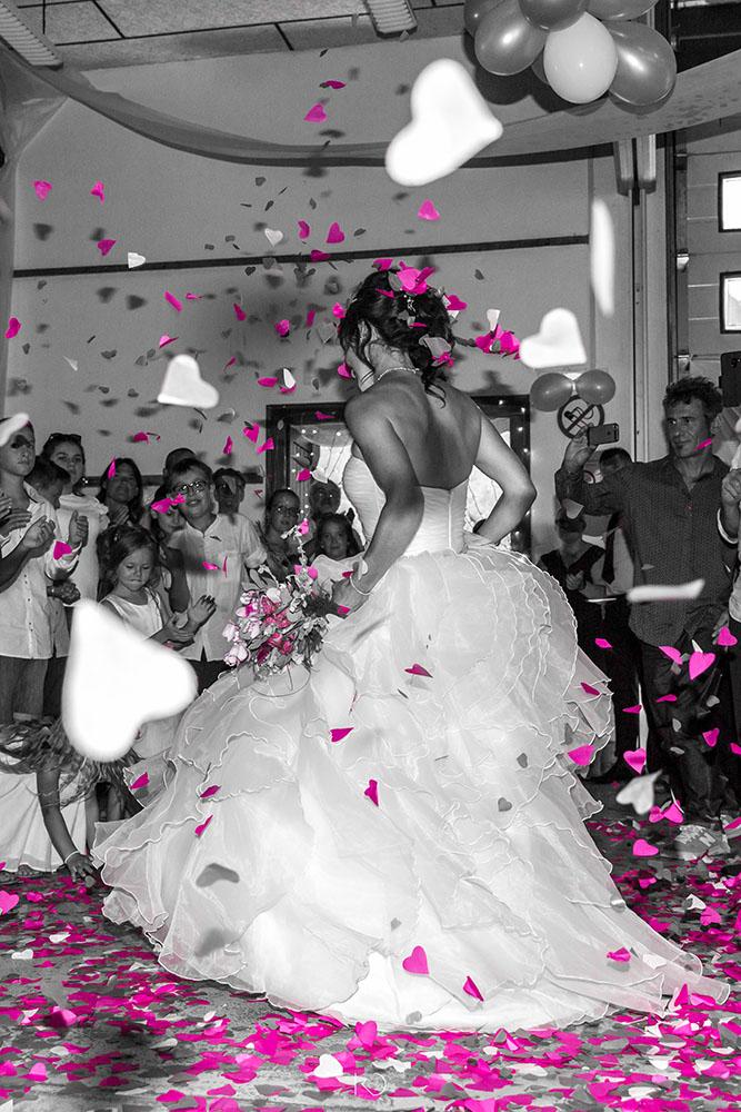 Mariée qui danse devant les invités sous une pluie de confettis rose et blanc en forme de coeur