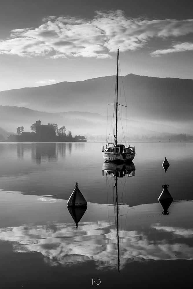photo noir et blanc d'un bateau au port de Talloires avec le chateau de Duingt en arrière plan
